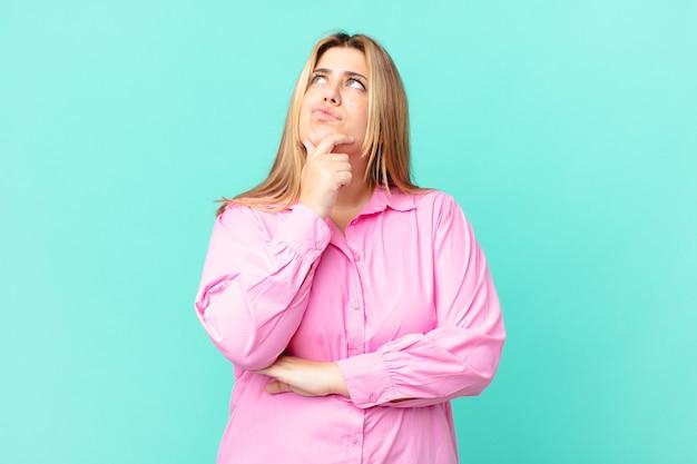 Krągła ładna blond kobieta myśli, czuje wątpliwości i jest zdezorientowana
