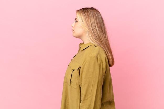 Krągła ładna blond kobieta na widoku profilu myśląca, wyobrażająca sobie lub marząca na jawie