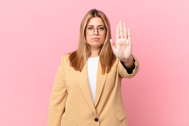 Krągła ładna blond kobieta wygląda poważnie pokazując otwartą dłoń, robiąc gest zatrzymania