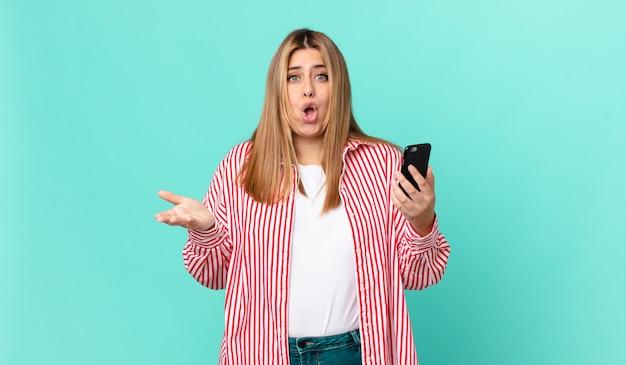 Krągła ładna blondynka czuje się bardzo zszokowana i zaskoczona i trzyma smartfona
