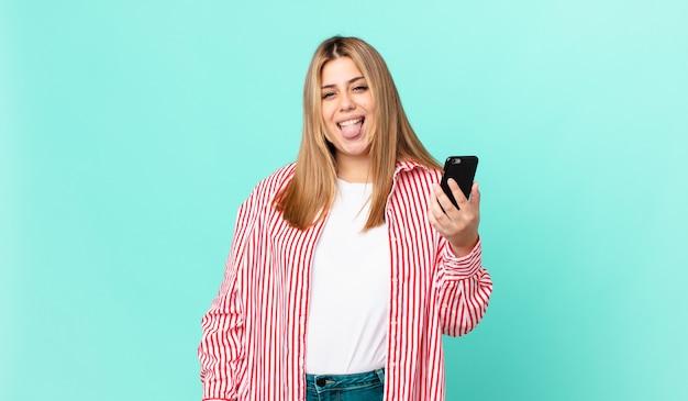 Krągła, ładna blondynka o wesołym i buntowniczym nastawieniu, żartująca, wystawiająca język i trzymająca smartfona