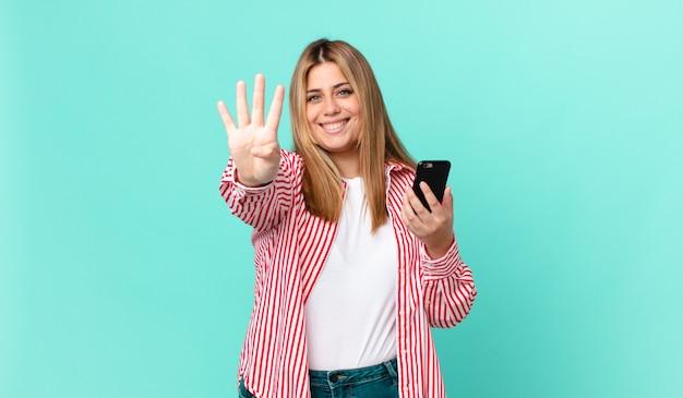 Krągła ładna blondynka uśmiecha się i wygląda przyjaźnie, pokazuje numer cztery i trzyma smartfona