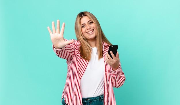 Krągła ładna blondynka uśmiecha się i wygląda przyjaźnie, pokazuje numer pięć i trzyma smartfona