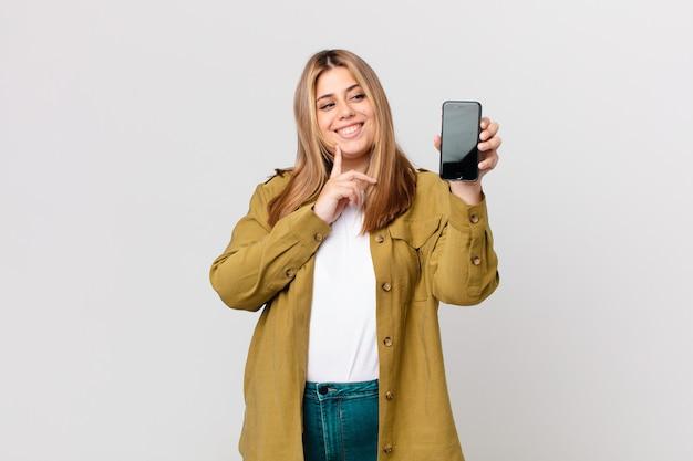 Krągła ładna blondynka uśmiecha się radośnie i marzy lub wątpi i trzyma smartfon
