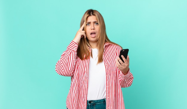 Krągła, ładna blondynka wygląda na zaskoczoną, realizując nową myśl, pomysł lub koncepcję i trzymającą smartfona
