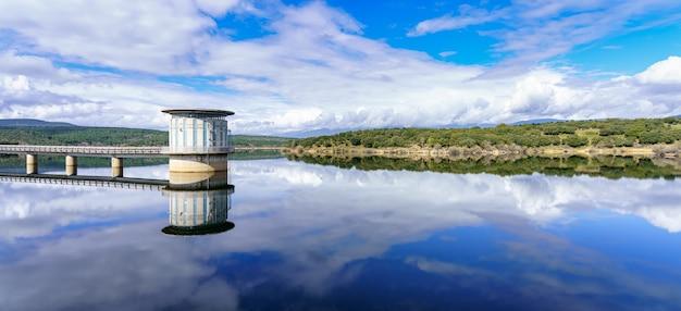 Krajobraz błękitnego jeziora i zielonych roślin z odbiciami w wodzie, bagienna wieża wodociągowa. atazar madryt,