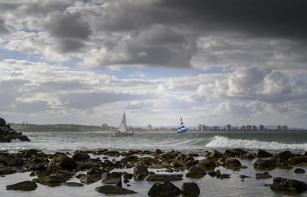 Krajobraz brzegu otoczonego morzem ze statkami i surferami na nim pod zachmurzonym niebem