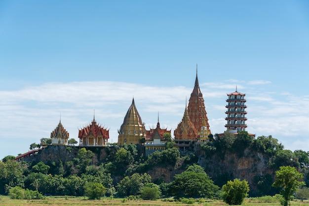 Krajobraz bujnego zielonego pola i otaczających gór w świątyni wat thum sua (świątynia jaskini tygrysa) w kanchanaburi, tajlandia