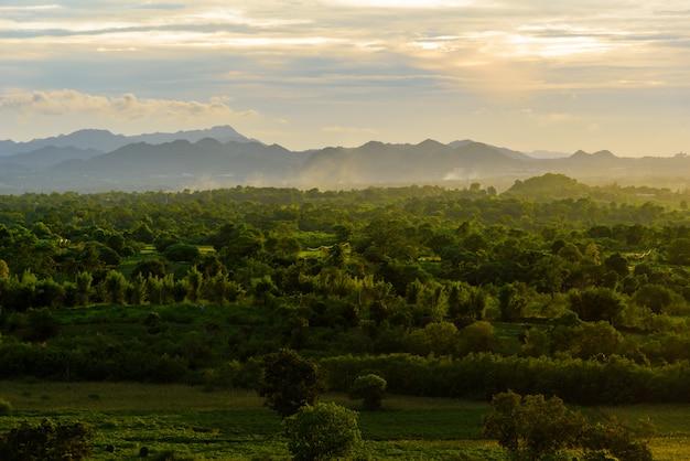 Krajobraz chmurny, góra i las z zmierzchem w wieczór od odgórnego widoku.