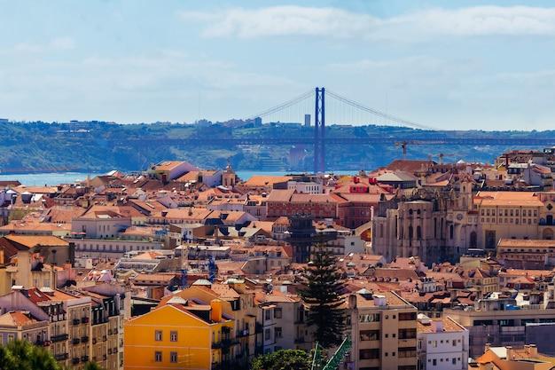 Krajobraz czerwoni dachy i odległy most nad rzeką w lisbon podczas słonecznego dnia