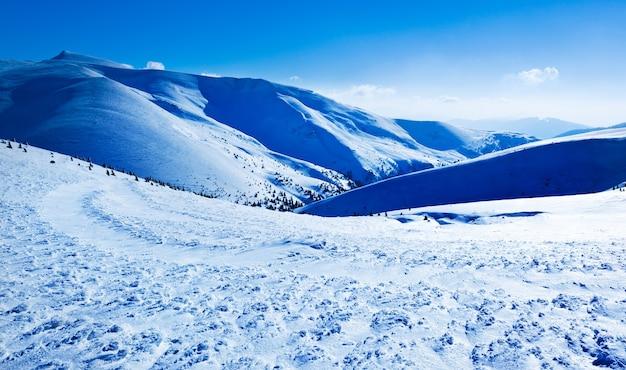 Krajobraz doliny śniegu i góry i słońce powyżej w jasny zimowy mroźny dzień