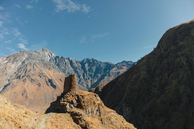 Krajobraz gergeti wierza ruiny na góry kazbek śladzie w stepansminda, kazbegi, gruzja.