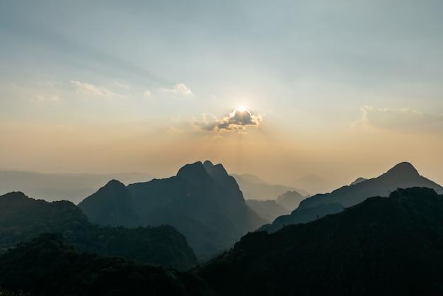 Krajobraz gór, chmury z promieniami słońca o zmierzchu