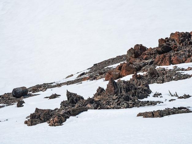 Krajobraz góralski z ostrzonymi kamieniami o nietypowym kształcie. niesamowity malowniczy górski krajobraz z dużym zbliżeniem pęknięty spiczasty kamień wśród śniegu pod błękitnym niebem w słońcu. ostre skały.