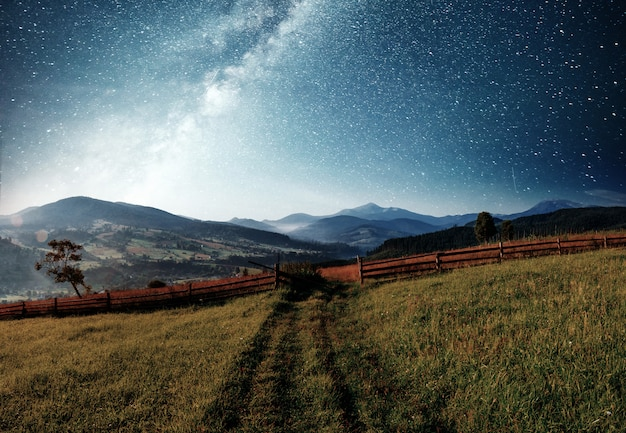 Krajobraz górski lato. wysoka trawa i żywe nocne niebo z gwiazdami, mgławicą i galaktyką. astrofotografia z głębokiego nieba