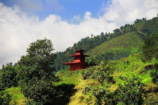 Krajobraz górski. mała czerwona pagoda na wzgórzu anadu. pokhara, nepal