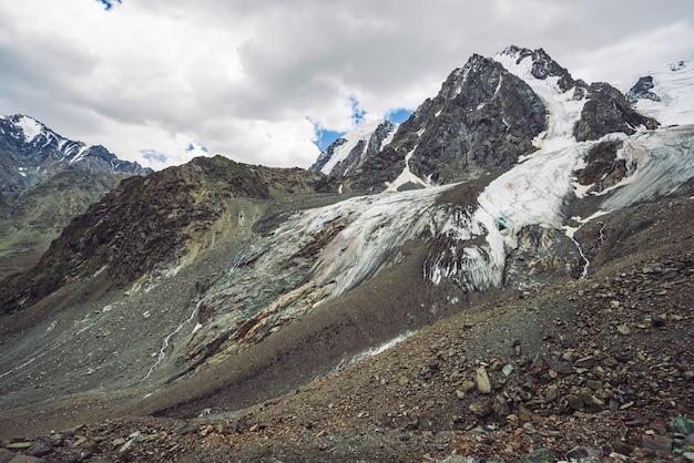 Krajobraz górski z lodowcem na szczycie góry i strumieniami wody w talusie