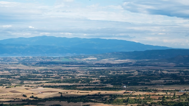 Krajobraz grecji, pola z zielenią, w oddali widoczne zielone wzgórza, pochmurna pogoda