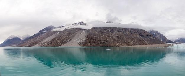 Krajobraz grenlandii z pięknymi kolorowymi górami i górą lodową.