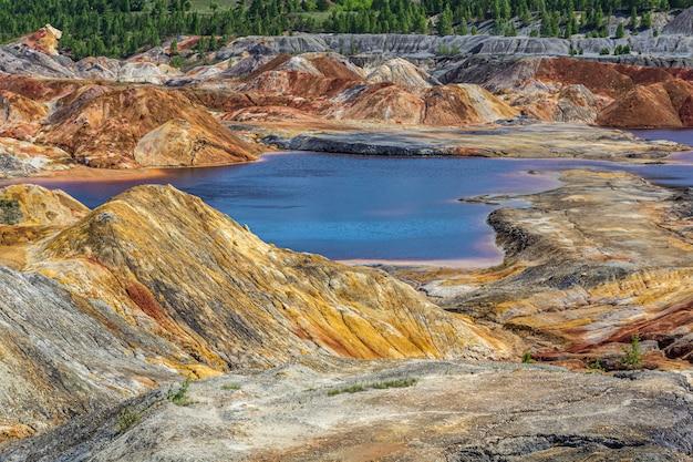 Krajobraz jak powierzchnia planety mars. uralskie kamieniołomy ogniotrwałe. natura uralu, rosja. zestalona czerwono-brązowa czarna powierzchnia ziemi do wygaszacza ekranu na pulpit, baner, okładka.