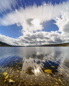 Krajobraz jeziora ze skałami pod przezroczystą wodą i wielkimi chmurami zanikającymi w niebo z odbiciami w wodzie. madryt.