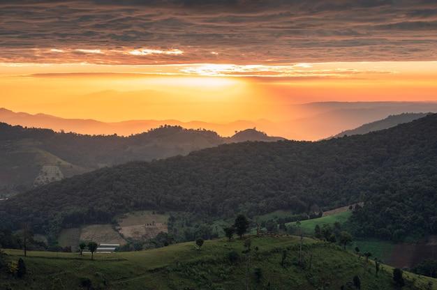 Krajobraz kolorowy wschód słońca nad górskimi polami uprawnymi w okolicy w doi mae tho, tajlandia