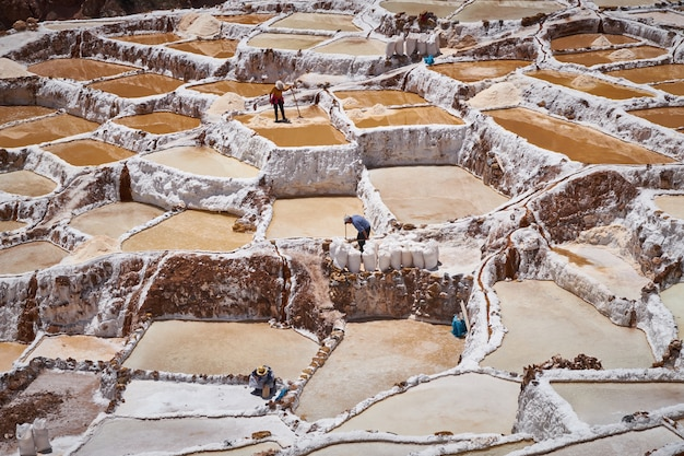 Krajobraz kopalni soli w maras i ich pracowników w regionie cusco, peru, sacred valley