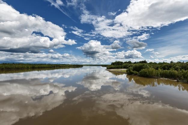 Krajobraz lato krajobraz kolorowy widok rzeki piękne błękitne niebo z chmurami odbicie w wodzie