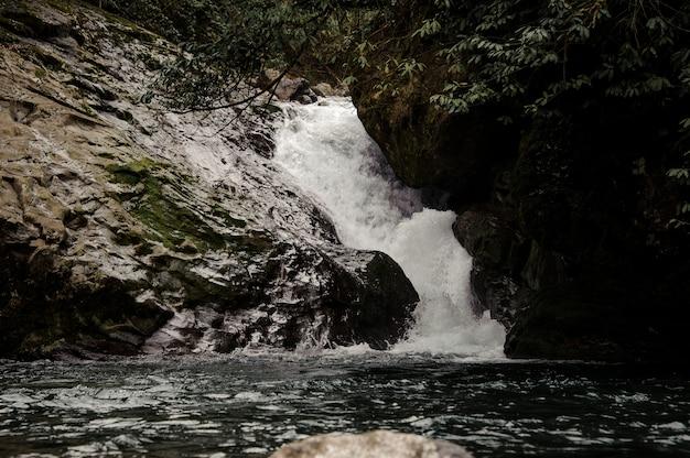 Krajobraz małego wodospadu w pobliżu jeziora otoczonego skałami w łaźniach afrodyty w gruzji