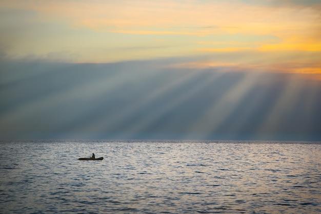 Krajobraz morski z łodzią przed dramatycznym zachodem słońca