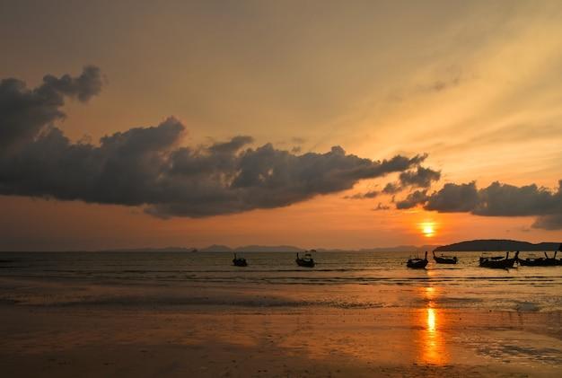 Krajobraz morski zachód słońca z tradycyjnymi tajskimi łodziami longtail i dramatycznym pochmurnym niebem