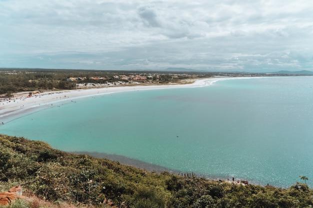 Krajobraz morza otoczony wyspą pokrytą zielenią pod zachmurzonym niebem