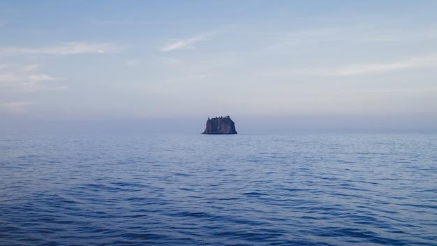 Krajobraz morza ze skałą pod pochmurnym niebem w ciągu dnia