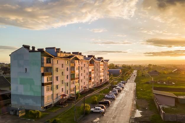 Krajobraz na przedmieściach z apartamentowcem i zaparkowanymi samochodami wzdłuż złej drogi