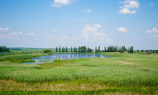 Krajobraz nieba z chmurami i jeziorem porośniętym trzciną latem i domem z czerwonym dachem i drzewami w oddali
