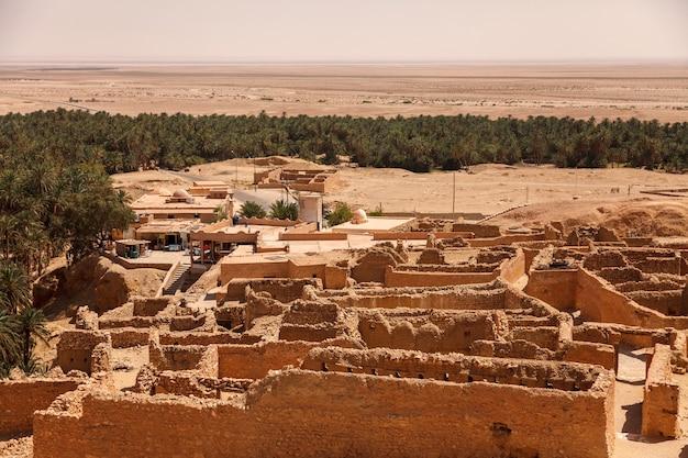 Krajobraz oazy chebika na saharze. ruiny osady i palmy. malowniczy widok górska oaza w afryce północnej. położony u stóp jebel el negueba. góry atlas w słoneczne popołudnie. tozeur, tunezja