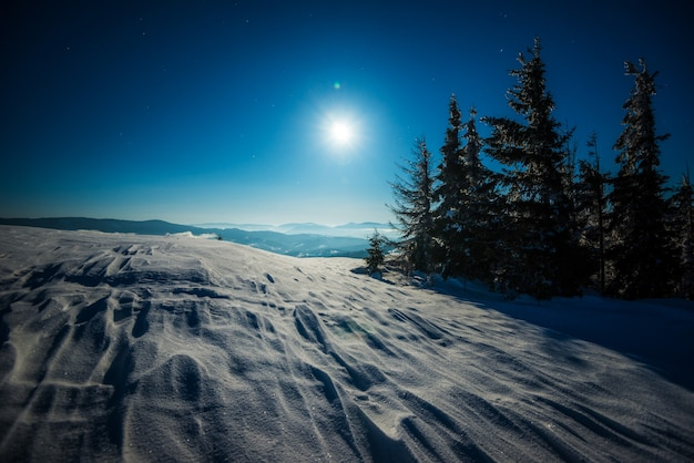 Krajobraz ośnieżonego stoku narciarskiego na tle świerkowego lasu i pasm górskich w świetle księżyca
