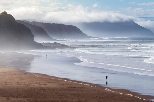 Krajobraz plaży obmywanej przez fale w odcieniach błękitu, w tle mgła i chmury oraz osoba spacerująca wzdłuż brzegu plaży. vizcaya, kraj basków. hiszpania.
