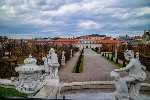 Krajobraz przed unteres belvedere z marmurowymi starożytnymi posągami i rzeźbami na czele na tle pochmurnego, jesiennego, szarego nieba w wiedniu, austria.