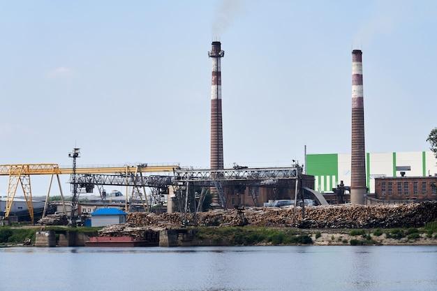 Krajobraz przemysłowy, celulozownia i papiernia ze stosami kłód i kominami nad rzeką