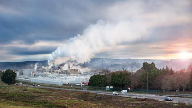 Krajobraz przemysłowy fabryczny dym unosi się o wschodzie słońca, zanieczyszczając atmosferę. koncepcja zanieczyszczenia