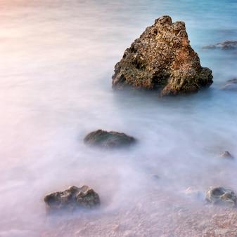 Krajobraz przyrody morza i skały o zachodzie słońca.