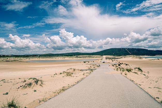 Krajobraz pustej drogi, kilka wzgórz na horyzoncie i puszyste chmury na niebie