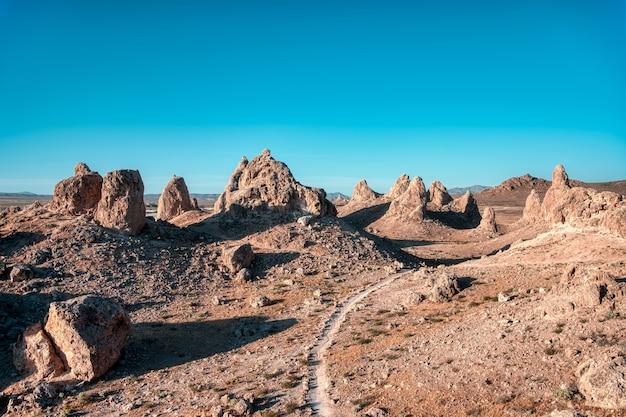 Krajobraz pustyni z pustą drogą i klifami pod bezchmurnym niebem