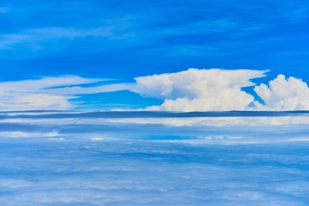 Krajobraz puszystych białych chmur na ciemnoniebieskim niebie. widok z samolotu na dużej wysokości.