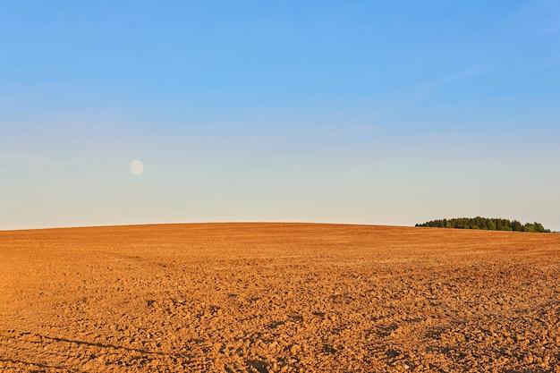 Krajobraz rolniczy wieczorne zaorane pole oświetlają promienie zachodzącego słońca