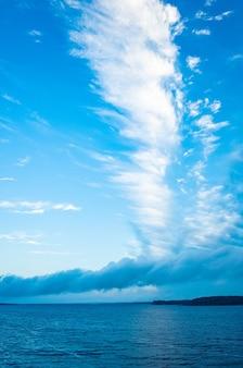 Krajobraz rzeczny spokojna woda i wielka biała piękna chmura o nietypowym kształcie skopiuj przestrzeń