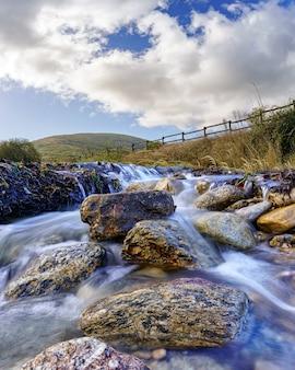 Krajobraz rzeczny z dużymi granitowymi skałami obmywanymi bieżącą wodą, chmurami na niebie i zielonymi roślinami. zdjęcie szerokokątne, długi czas naświetlania. lozoya, madryt.