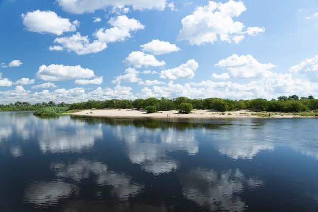 Krajobraz rzeka z błękitnym niebem i chmurami odbija się w wodzie w letni dzień.