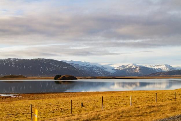 Krajobraz rzeki otoczonej wzgórzami pokrytymi śniegiem i odbijających się w wodzie w islandii